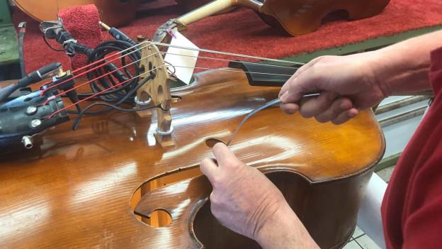 Mark Schuler setzt einen Stimmstock in den Bass ein.