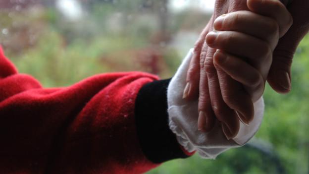 Frauenhand hält Hand eines Kindes.