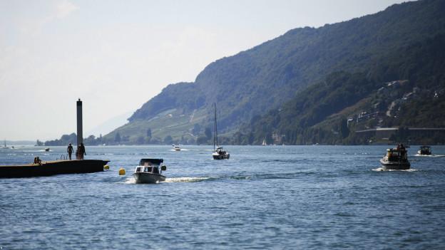 Menschen geniessen das warme Wetter auf Booten am Bielersee in Biel.