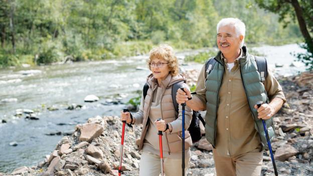 Eine Frau und ein Mann wandern einem Fluss entlang.