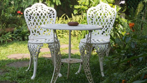 Zwei Stühle und ein Tisch stehen im Garten.