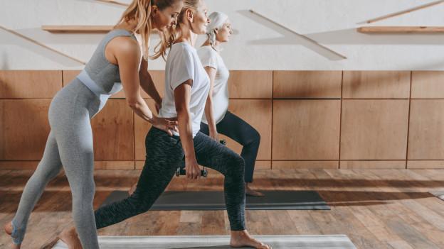 Eine Yoga-Lehrerin korrigiert die Haltung einer Kursteilnehmerin.