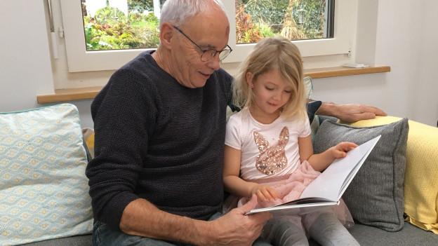 Ein Grossvater sitzt mit seiner Enkelin auf dem Sofa.