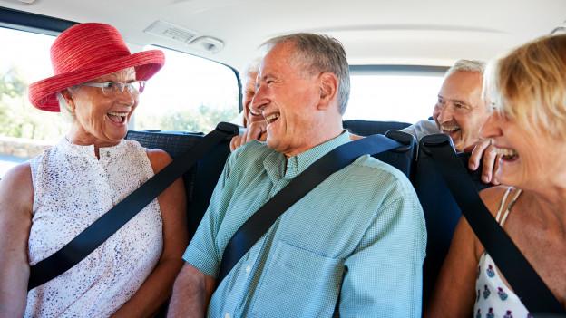 Senioren sitzen angeschnallt in Reisebus.
