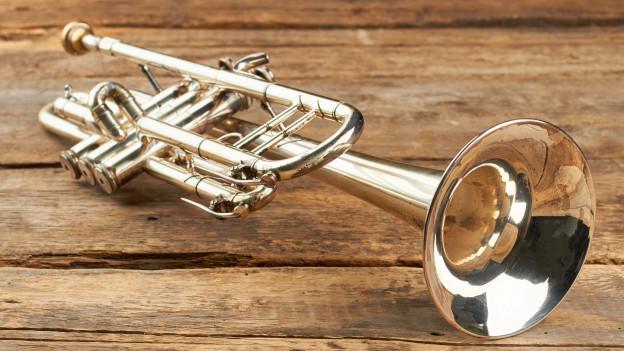 Eine Trompete liegt auf Holz.