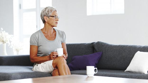 Seniorin sitzt alleine mit zwei Tassen Kaffee an einem Wohnzimmertisch.