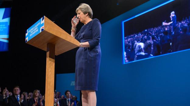 Theresa May trinkt einen Schluck Wasser.
