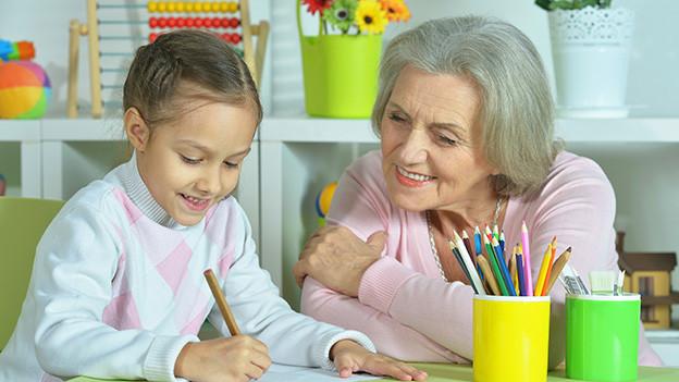 Eine Grossmutter macht Hausaufgaben mit ihrem Enkelkind.