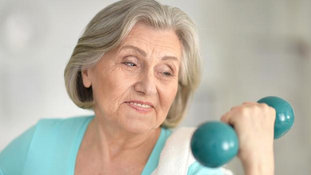 Eine ältere Frau mit einer Hantel in der Hand.