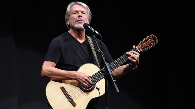Ein Sänger mit Gitarre auf einer Bühne.