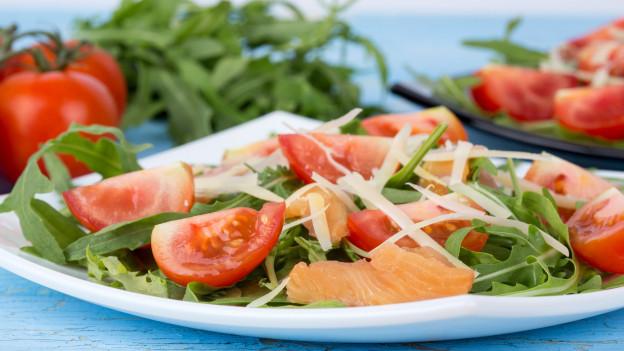 Ein Salat mit Ruccola, Tomaten, Käse und Lachs.