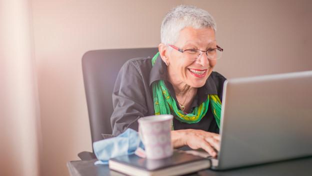 Aeltere Frau mit Brille am Laptop