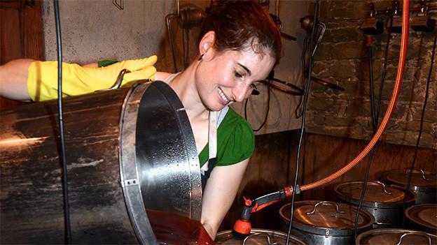 Eine Frau giesst farbige Flüssigkeit in einen Behälter.