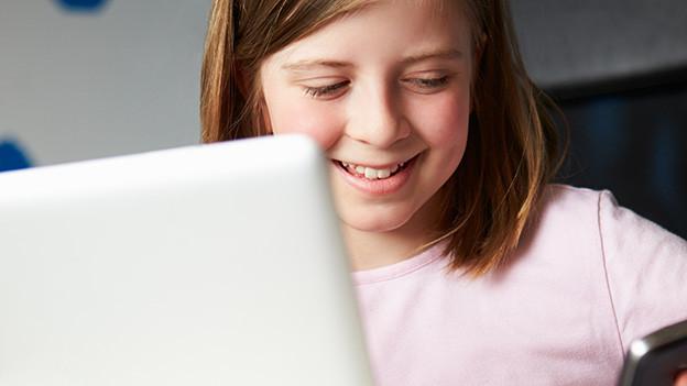 Ein Mädchen sitzt vor einem Laptop.