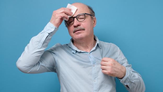Mann schwitzt und tupft sich die Stirne mit einem Tuch ab