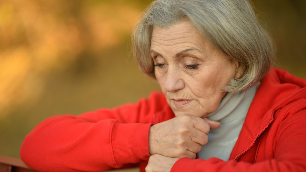 Nachdenkliche Seniorin in rotem Pullover.