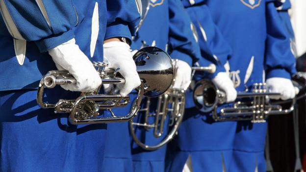 Blasmusikformation in blauen Kostümen.