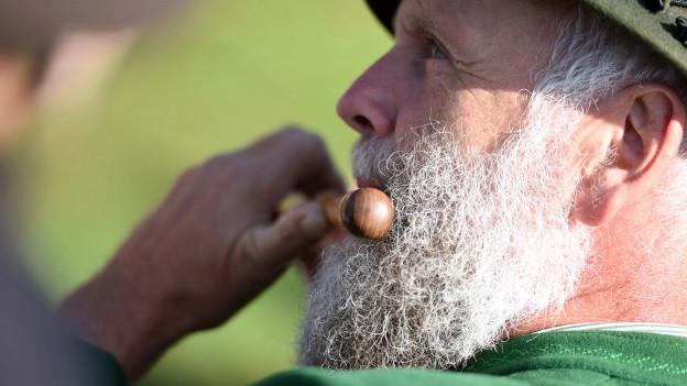 Ein Mann mit Bart spielt eine Schwegelpfeife.