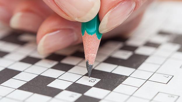 Eine Person löst ein Kreuzworträtsel.