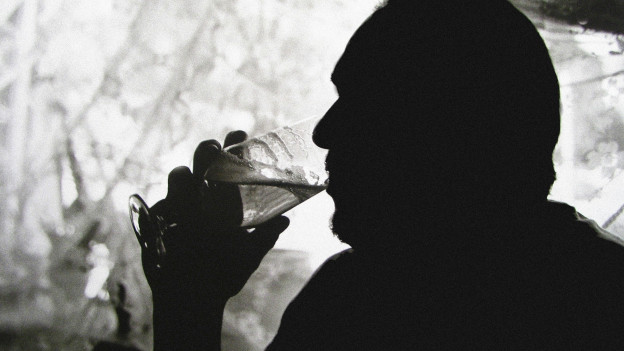 Eine Silhouette von einem Mann, der etwas trinkt.