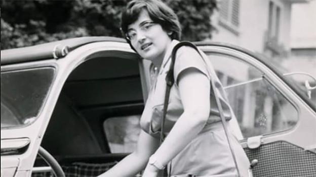 Eine junge Frau steigt ins Auto ein.