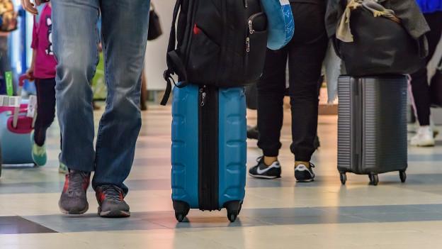 Reisende mit Koffer am Flughafen.