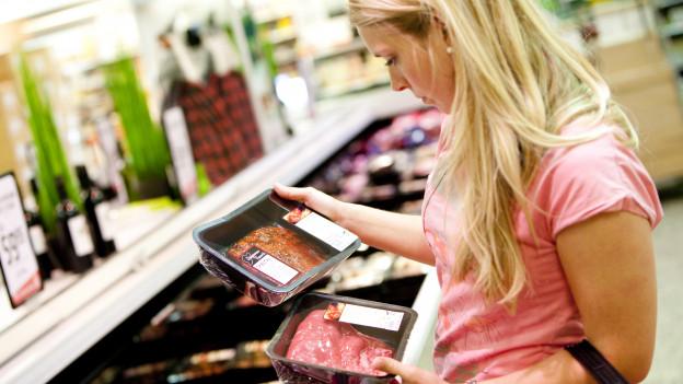 Eine junge Frau hält zwei verschiedene Packungen Fleisch in der Hand.