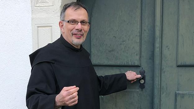 Ein Mönch vor einer Klostertüre.