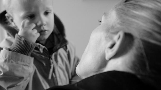 Ein Kind hört nachdenklich einem Erwachsenen zu.