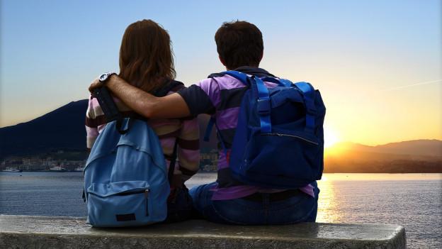 Pärchen mit Trecking-Rucksäcken sitzt auf Bank vor Sonnenuntergang.