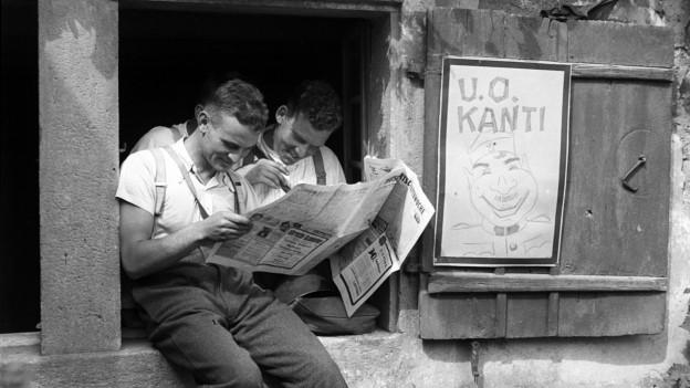 Soldaten der Schweizer Armee im Aktivdienst lesen vor der Unteroffizierskantine eine Zeitung, aufgenommen im Kriegsjahr 1939.