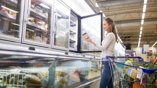 Eine junge Frau nimmt etwas aus dem Tiefkühler im Laden.