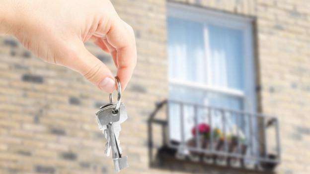 Eine Hand hält einen Schlüssel hoch, im Hintergrund ein Fenster eines Hauses.