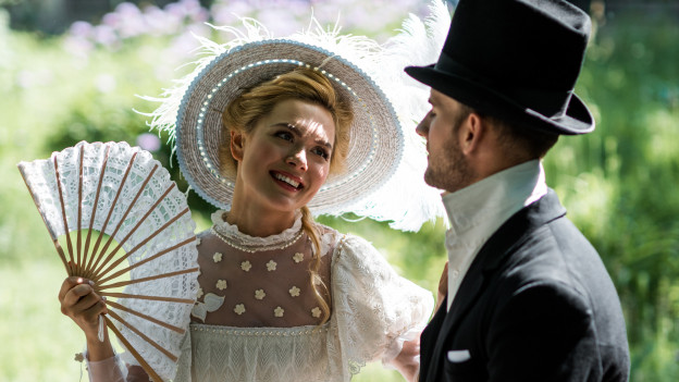 Paar in Kleidern der feinen Gesellschaft des 19. Jahrhunderts sitzt auf Bank in Park.