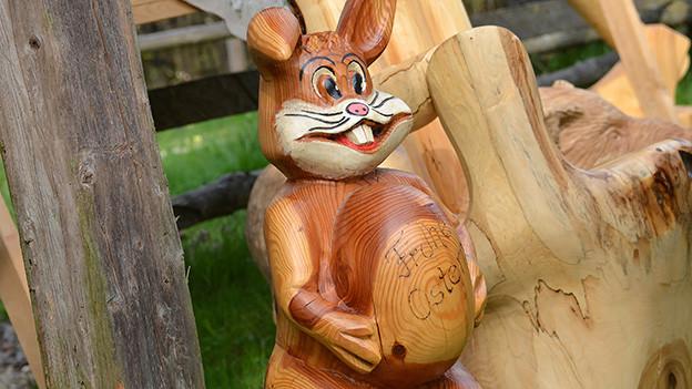 Ein Osterhase aus Holz mit einem Ei.