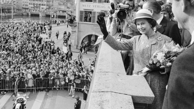 Queen steht auf Balkon und winkt den Massen zu.