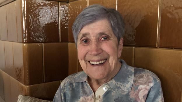 Eine ältere Frau sitzt auf dem Bänkli beim Kachelofen.
