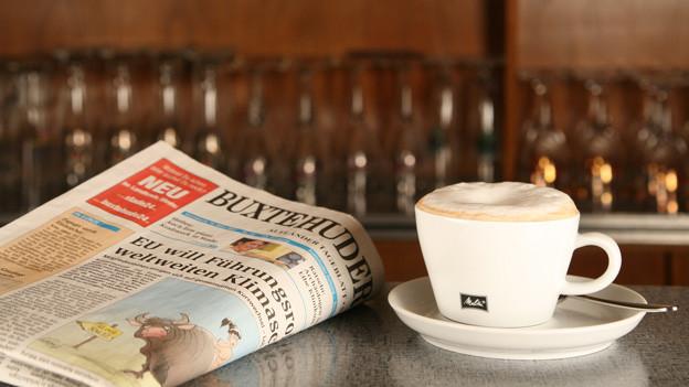 Tasse Kaffee steht auf Tresen in Kneipe, daneben eine aktuelle Tageszeitung.