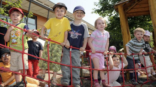 Einige Kinder stehen auf einer Hängebrücke.