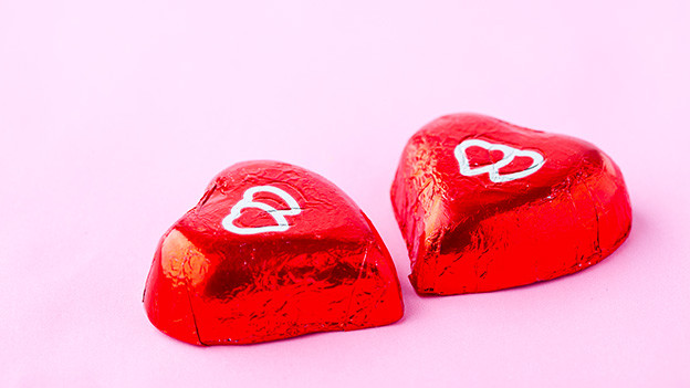 Zwei Schokoladeherzen in rotem Papier.