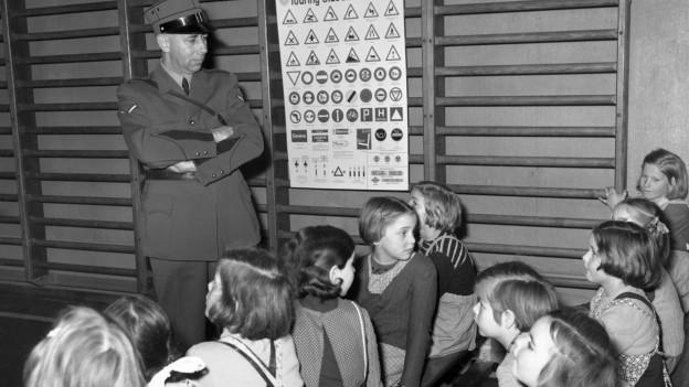 Ein Polizist erklärt Kindern die Verkehrstafeln.