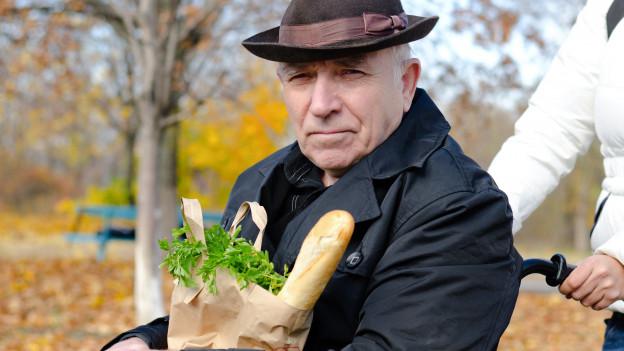 Senior im Rollstuhl mit Tüte voller Lebensmittel wird geschoben.