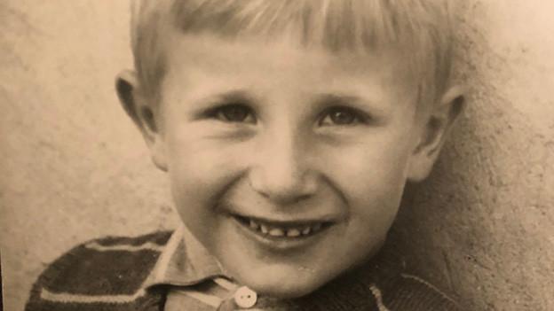 Ein lachendes Kind mit blonden Haaren.