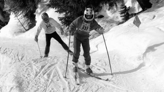 Zwei Skifahrer mit Helm beim Inferno Skirennen.