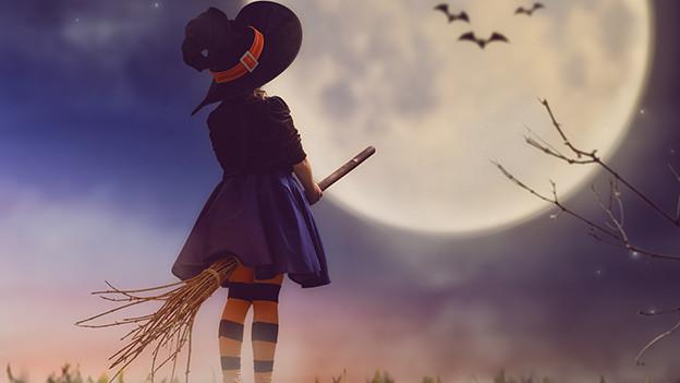 Ein kleines, als Hexe verkleidetes Mädchen, sitzt auf einem Besen.