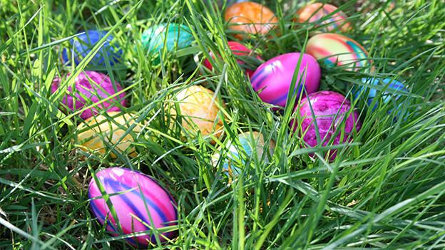 Gefärbte Eier liegen im Gras.