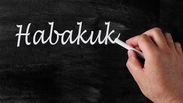Hand zeichnet Wort mit Kreide an Wandtafel.