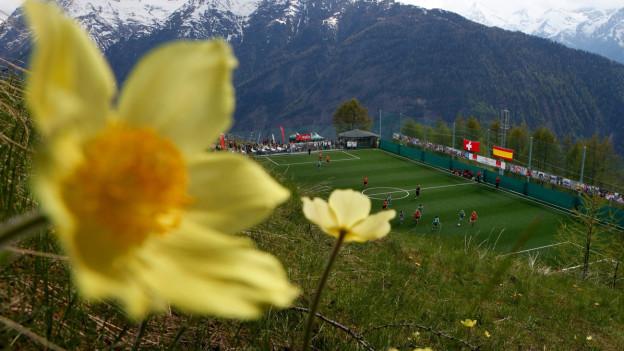 Blick auf einen Fussballplatz in den Bergen.