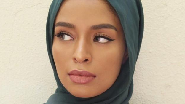Nahaufnahme eines Frauengesichts mit arabischen Zügen. Die Frau trägt Kopftuch.