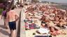 Blers turists che stan el sulegl a la riva da la mar.